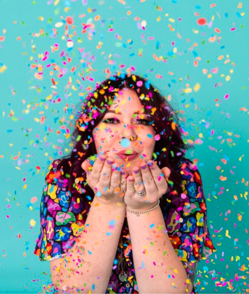 Image of Kasey Rainbow with confetti blowing around against turquoise background.